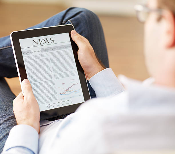 man reading news on the digital tablet stock photo