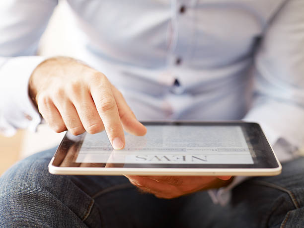 man reading news on the digital tablet - publication stock pictures, royalty-free photos & images