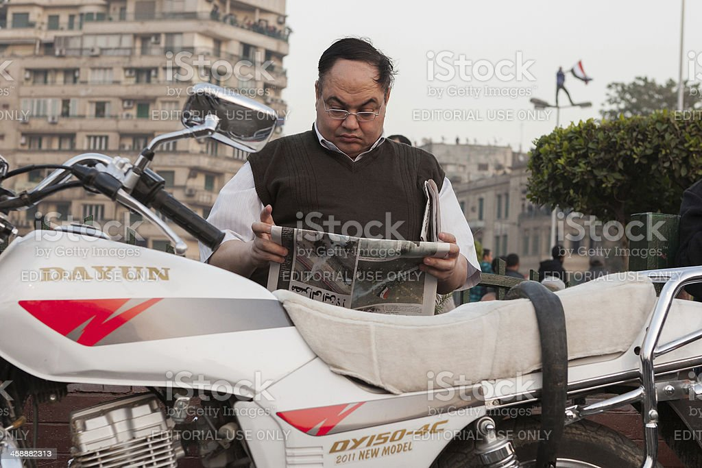 Man reading news paper about the clashes on Tahrir Square royalty-free stock photo