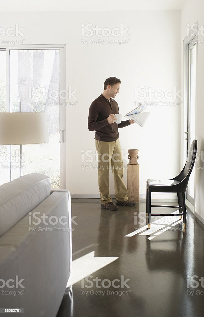 Man reading newspaper at home royalty-free stock photo