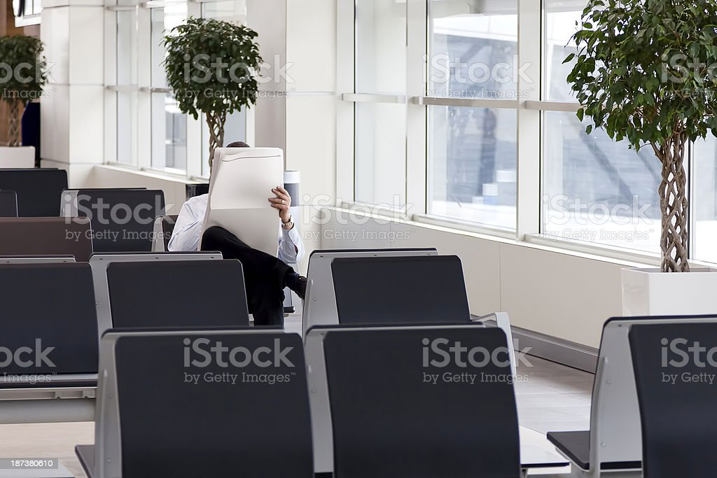 Man Reading Newspaper In Airport Lounge royalty-free stock photo