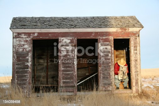 A Caucasian man reading a newspaper in an outhouse. Man is sitting in a bathroom in a rural setting and going to the bathroom. Man is wearing cowboy hat and squatting. He is unrecognizable. Image taken near Calgary, Alberta, Canada.