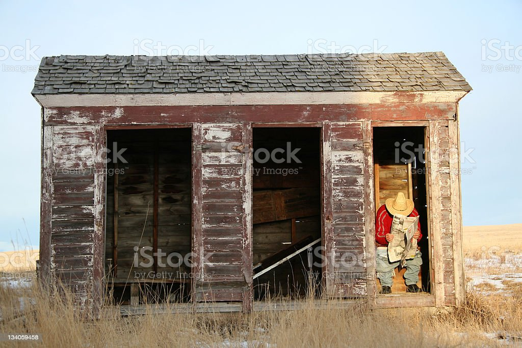 Man Reading Newspaper in an Outhouse stock photo