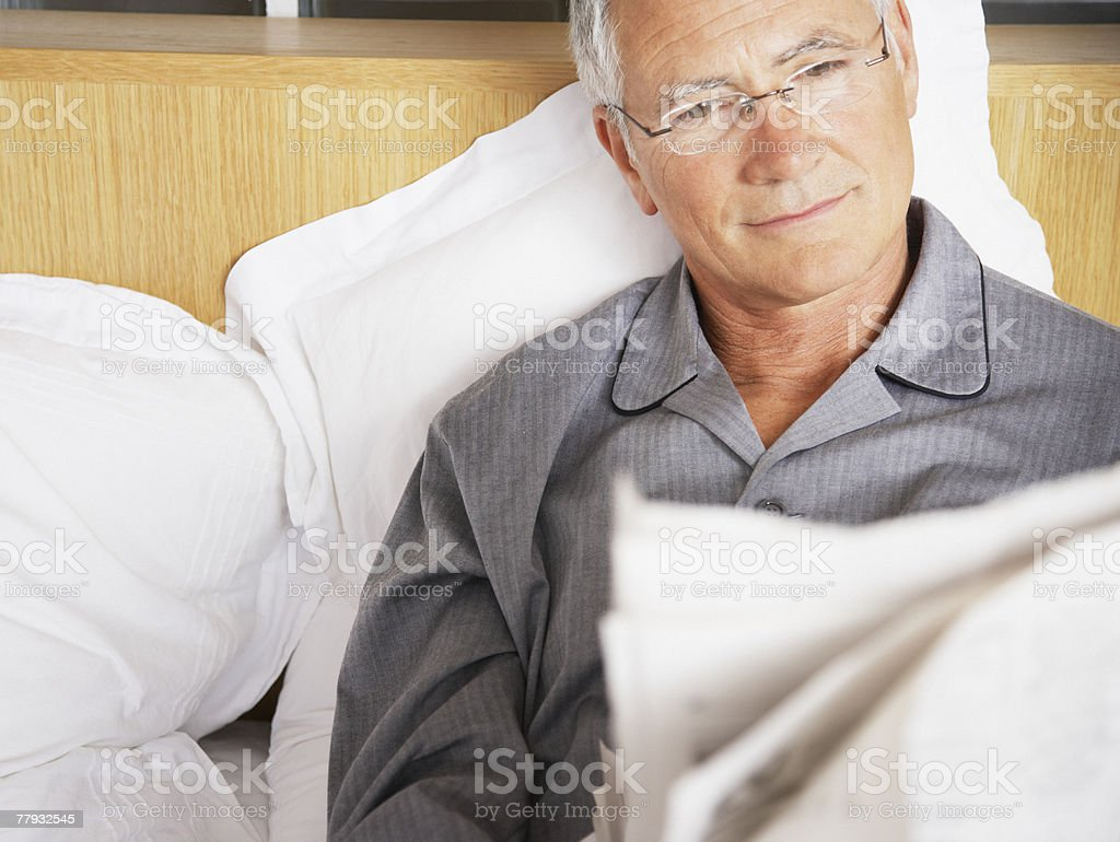 Man reading newspaper in bed royalty-free stock photo