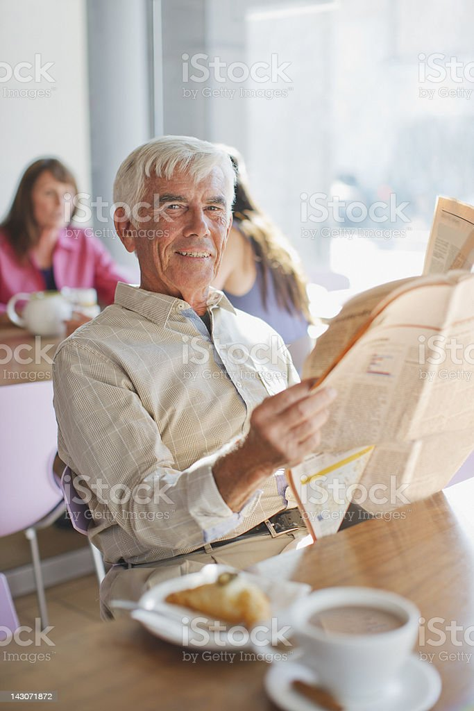 Man reading newspaper in cafe royalty-free stock photo