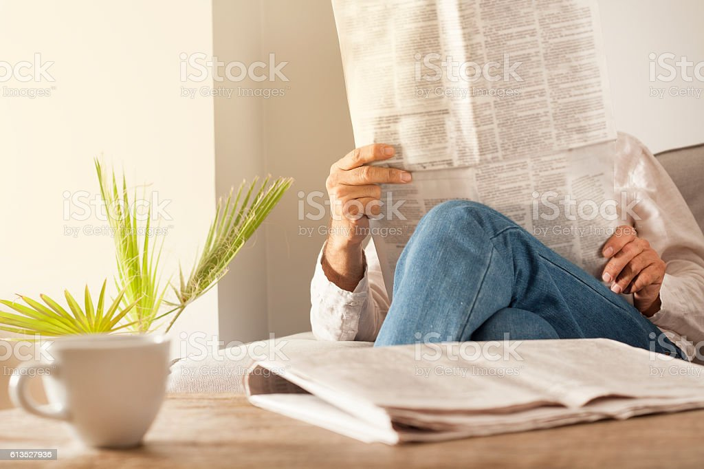 Man reading newspaper in home stock photo
