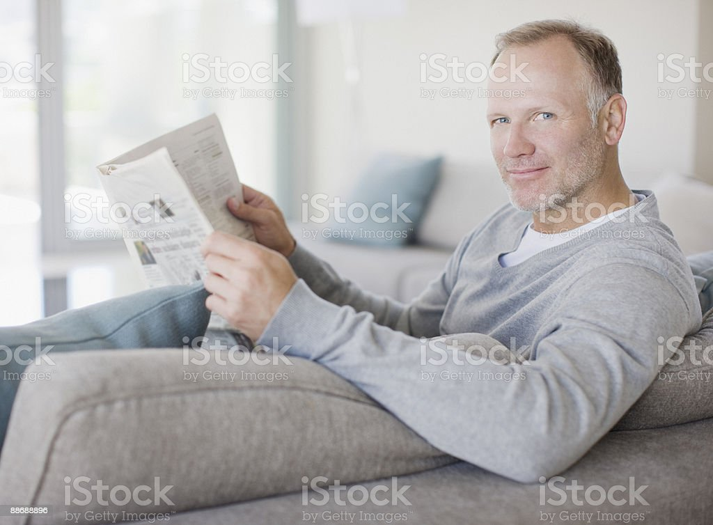Man reading newspaper in living room royalty-free stock photo