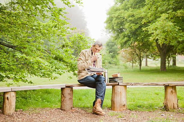 man reading newspaper in park - bench bildbanksfoton och bilder
