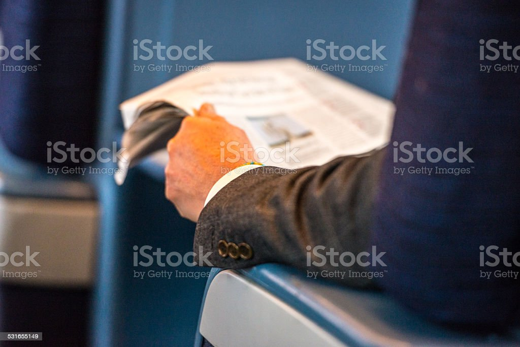 Man reading newspaper in train stock photo