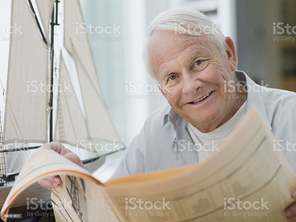Man reading newspaper near model sailboat royalty-free stock photo