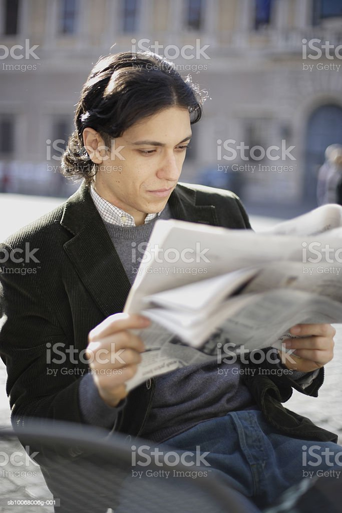 Man reading newspaper outdoors royalty-free stock photo