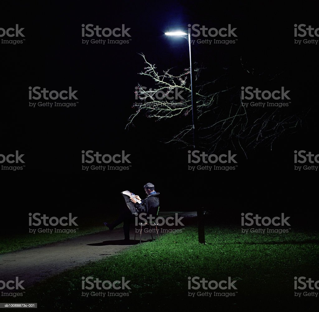 Man reading newspaper under street light in park at night foto de stock libre de derechos