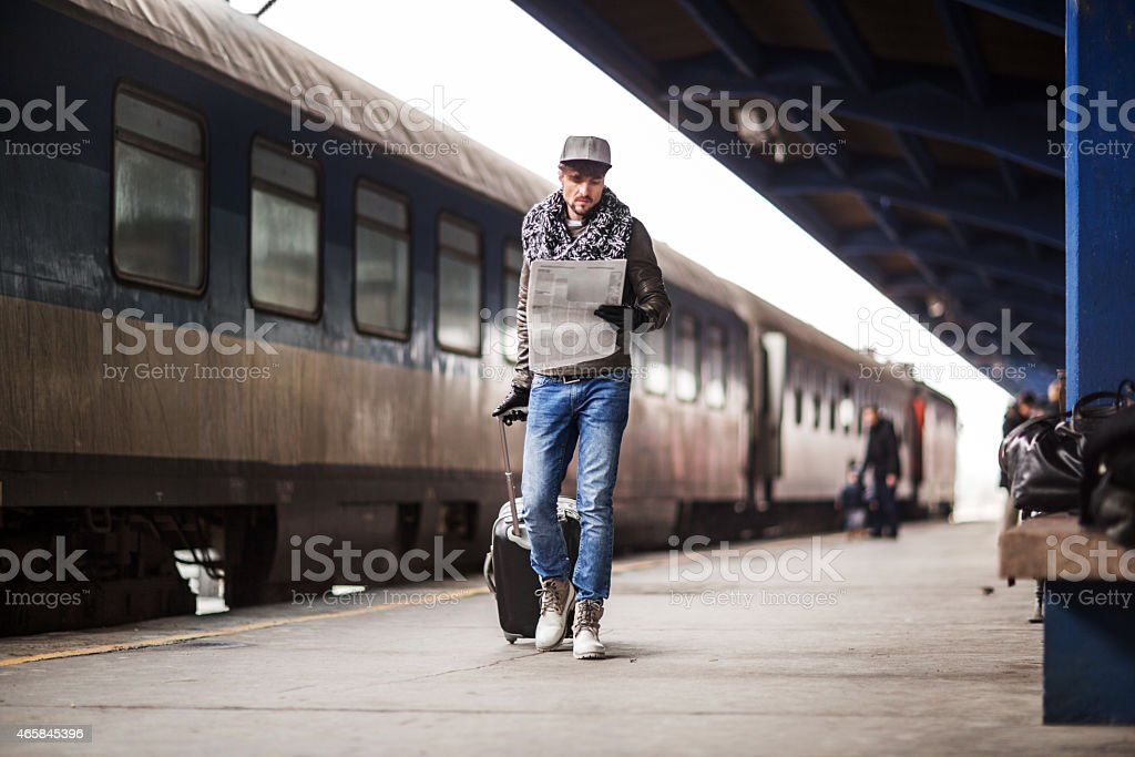 Man reading newspapers on train station. stock photo