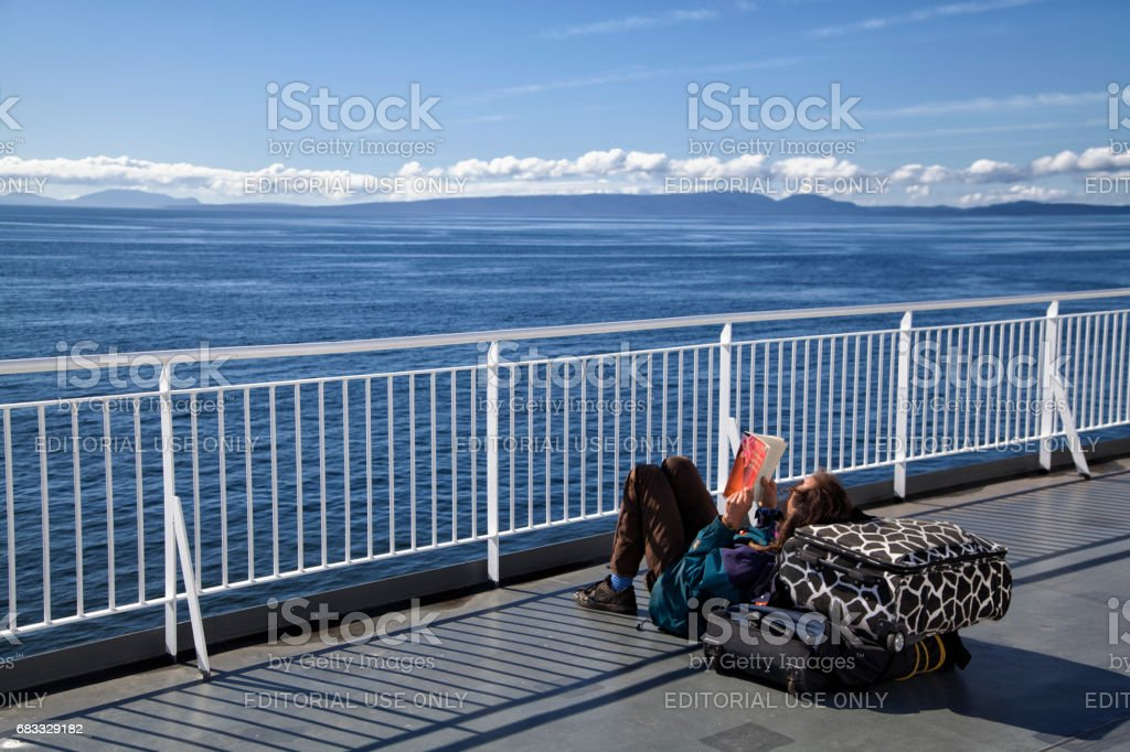 Man reading on the deck of a ferry, BC,Canada stock photo