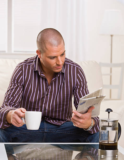 Man Reading Paper - Vertical A young, attractive man is sitting at a coffee table, drinking coffee and reading a newspaper.  He is looking away from the camera.  Vertically framed shot. shaved head stock pictures, royalty-free photos & images