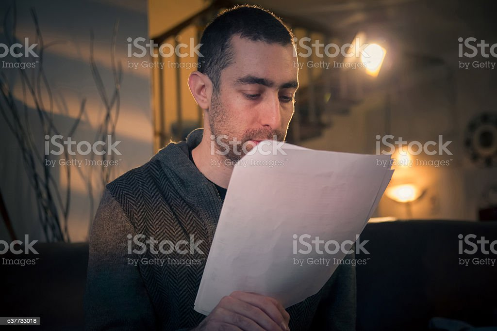 Man reading papers in a room stock photo