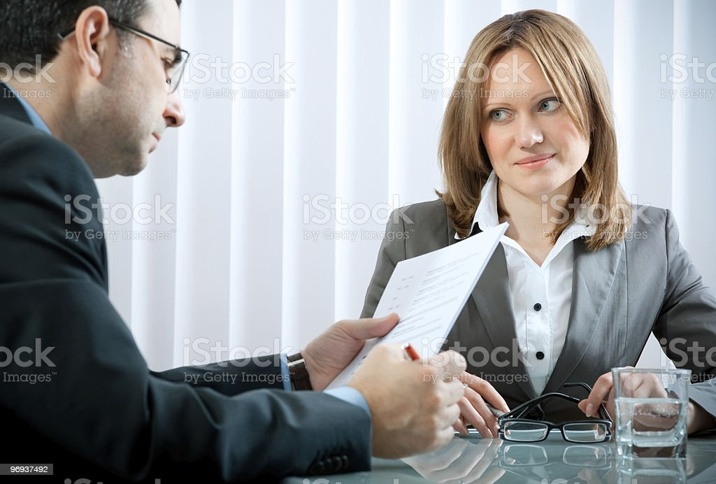 Man reading resume of lady at job interview Young woman having a job interview in a office. Adult Stock Photo