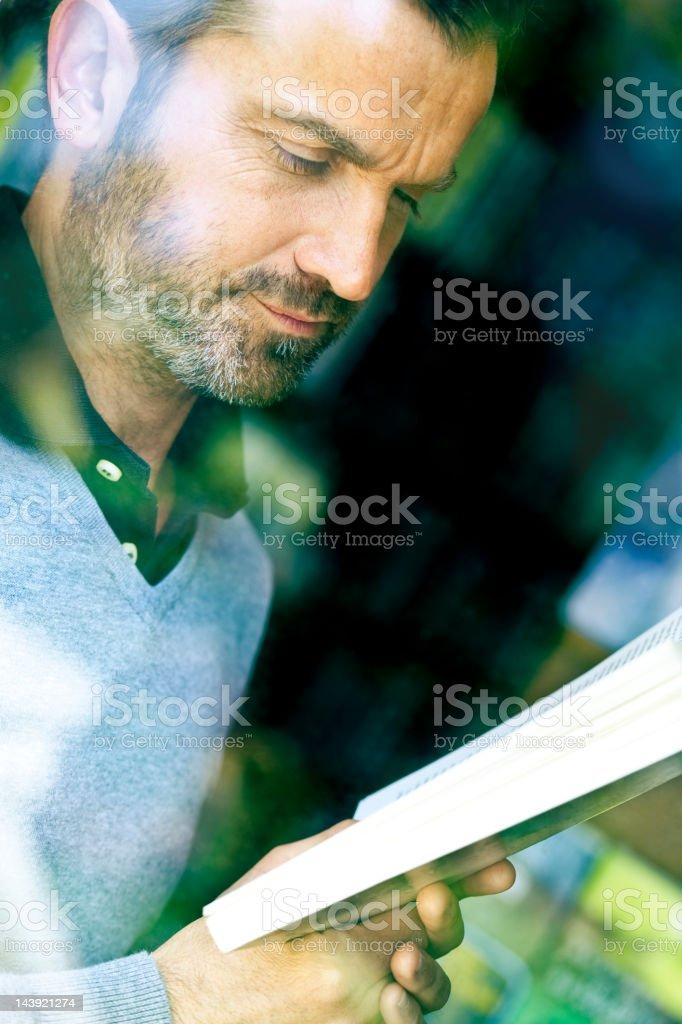 Man reading, seen through a window royalty-free stock photo
