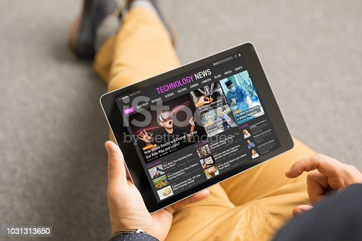 Top view of man reading technology news on tablet. All contents are made up.