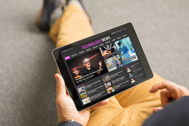 Man reading technology news on tablet. All contents are made up. Top view of man reading technology news on tablet. All contents are made up. article stock pictures, royalty-free photos & images
