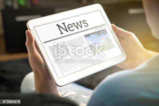 istock Man reading the news on tablet at home. Imaginary online and mobile news website, application or portal on modern touch screen display. 873384676