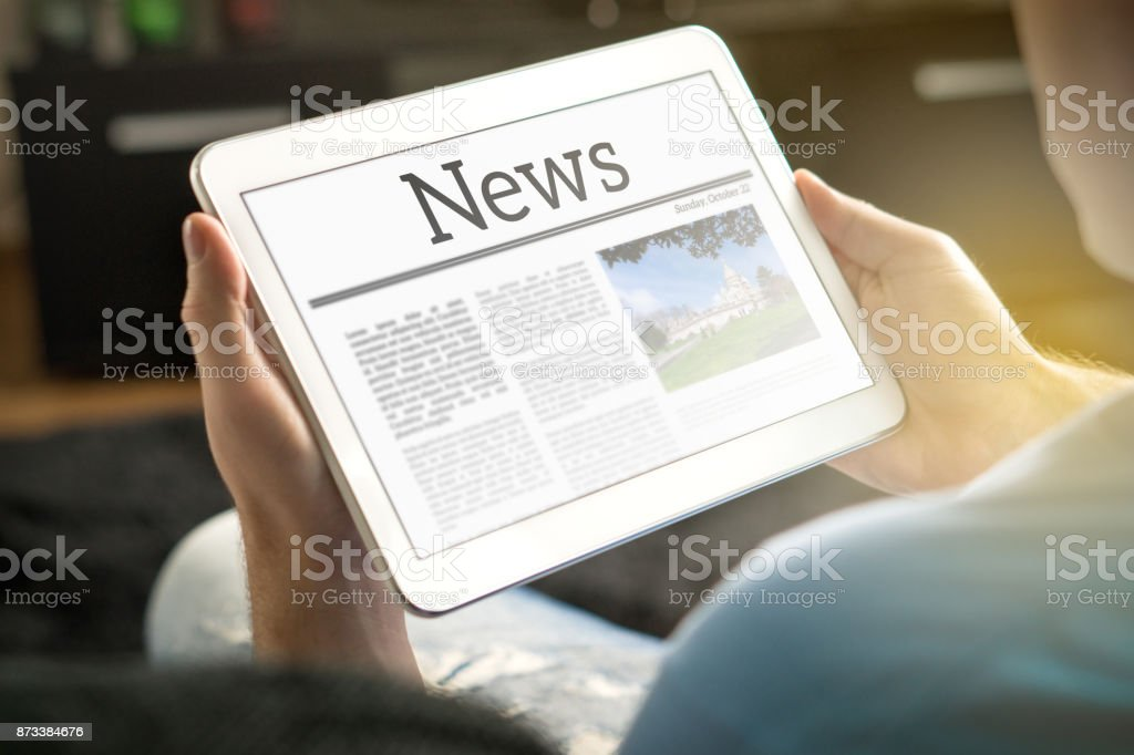 Man reading the news on tablet at home. Imaginary online and mobile news website, application or portal on modern touch screen display. stock photo