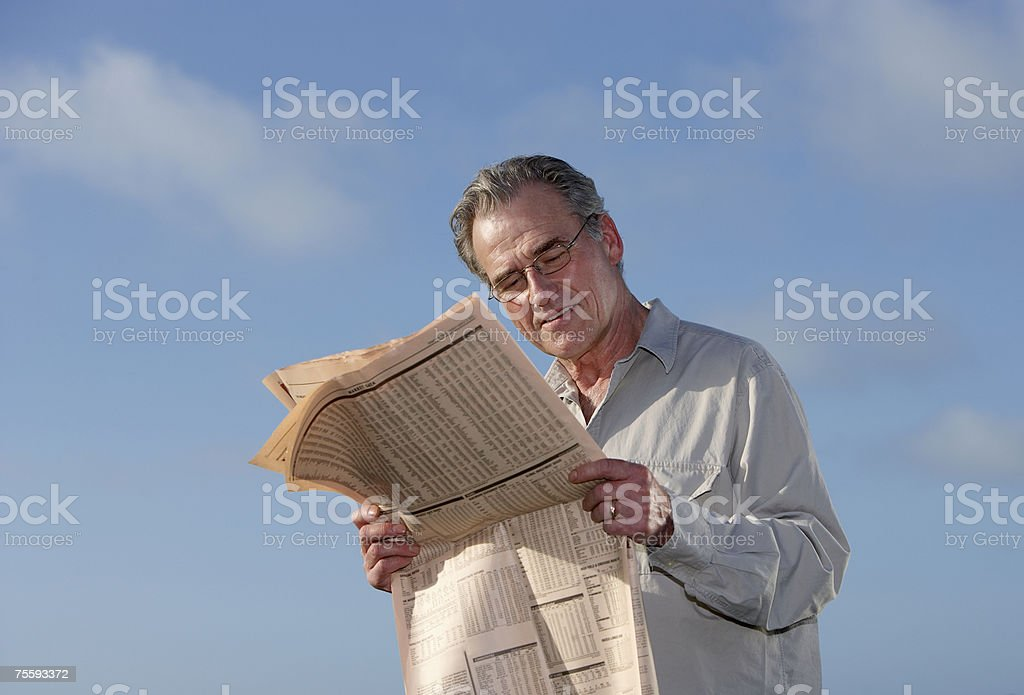 Man reading the paper outdoors royalty-free stock photo