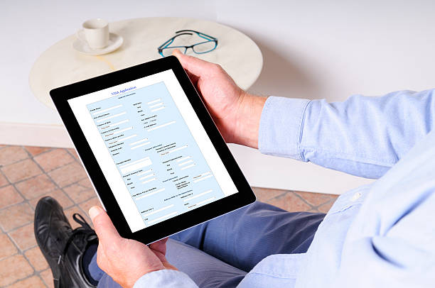 Man Reading Visa Application on Digital Tablet stock photo