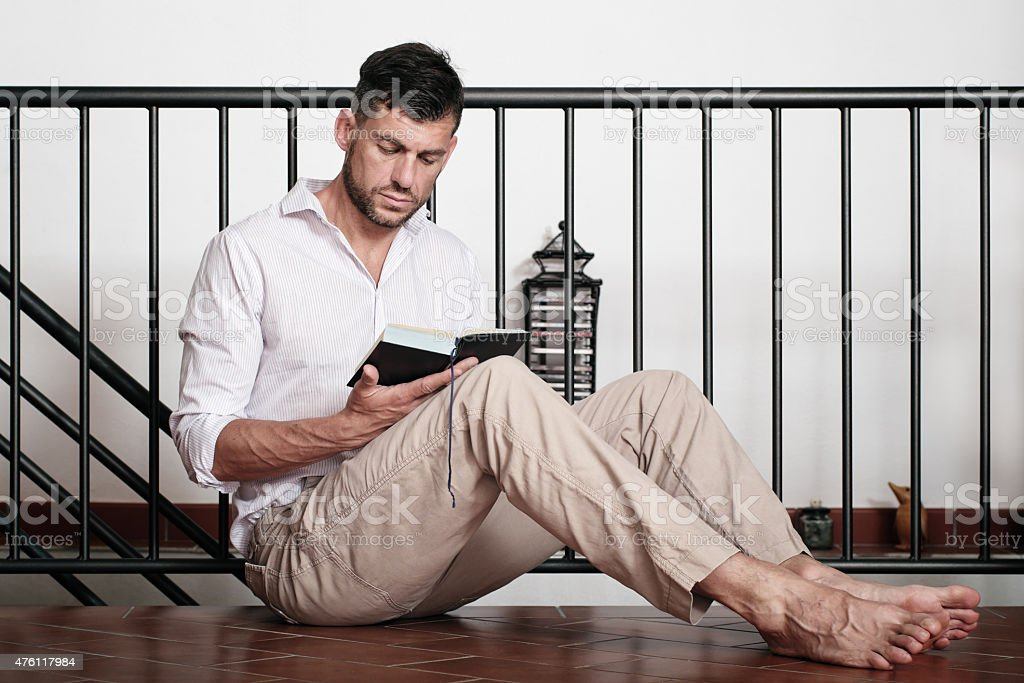 Mann liest ein Buch zu Hause sitzen auf dem Boden – Foto