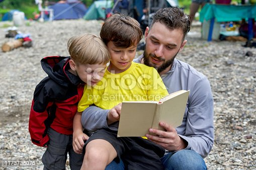 A man reads a book to two boys while camping. The eldest son sits on his father