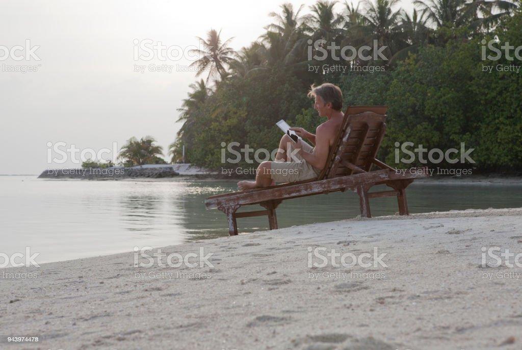 De Homme Au Dipad Sur Une Chaise Longue Droit Lit Photo Libre UzMGqSVp