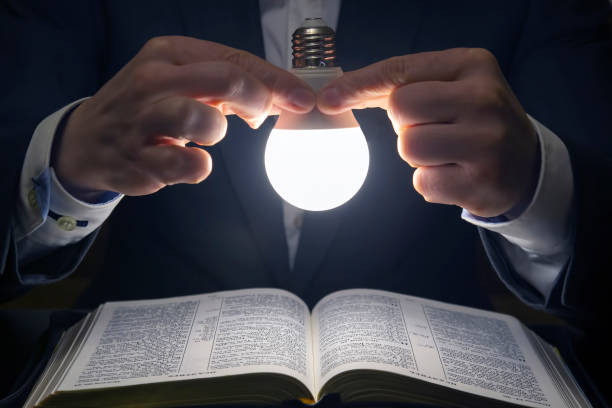 man reads the holy bible in the light of the LED lamp on. the search for God and the study of the book. Christianity and religion stock photo