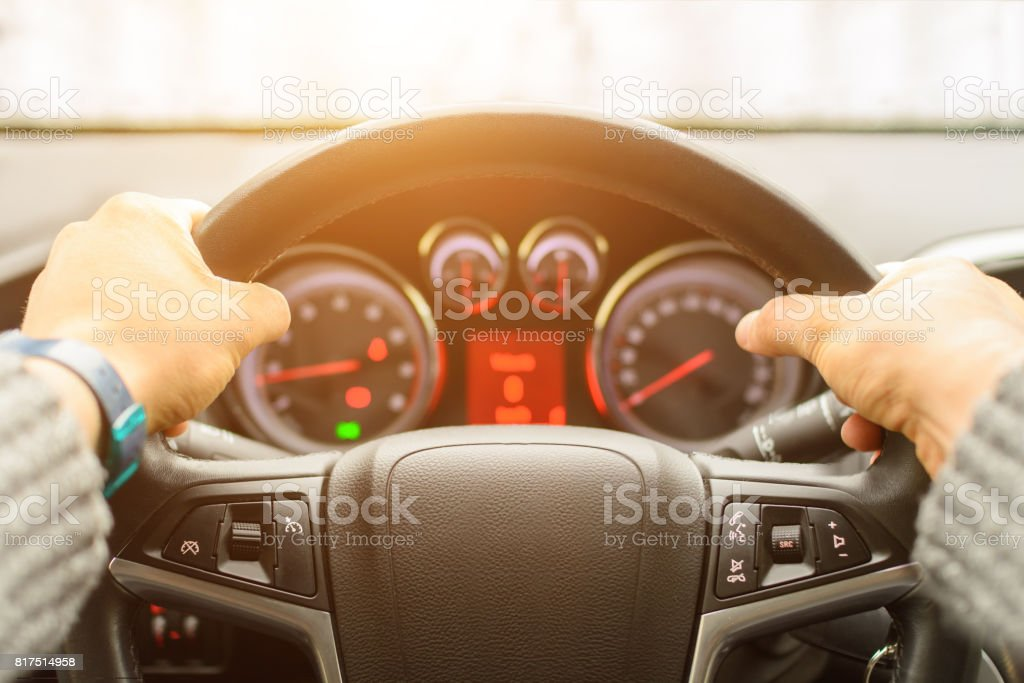 Man ready for driving the car on the freeway. Close up of hands of driver on steering wheel of car. Personal point of view of machine's stock photo