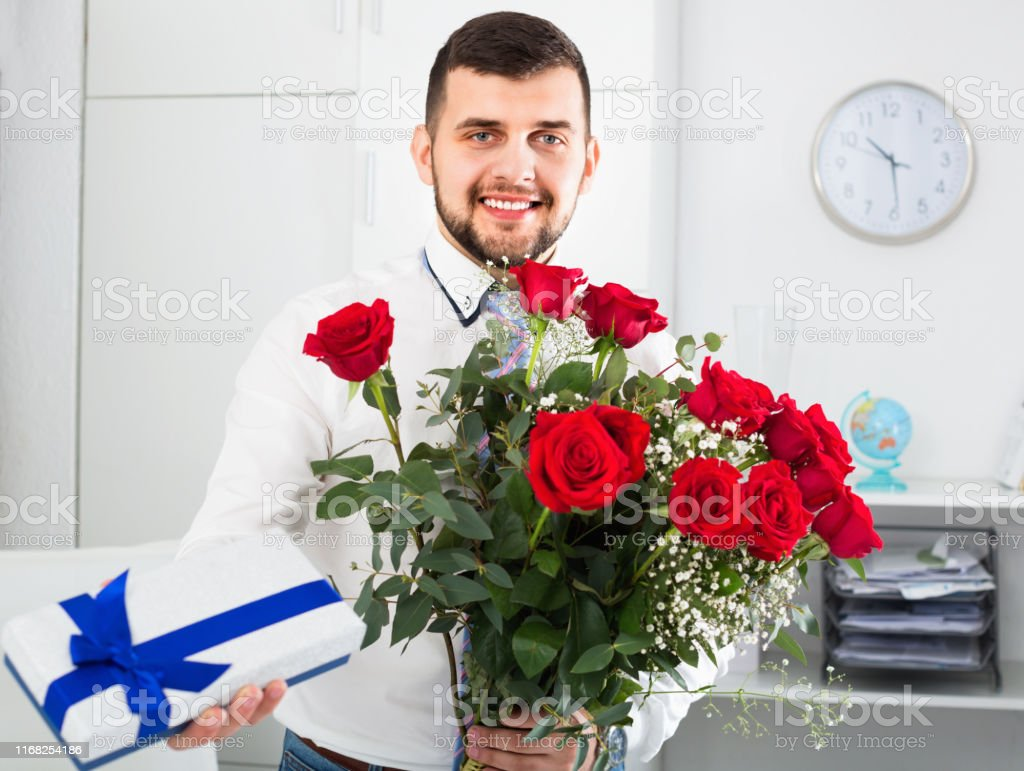Young positive man ready to present flowers and gift at holiday in...