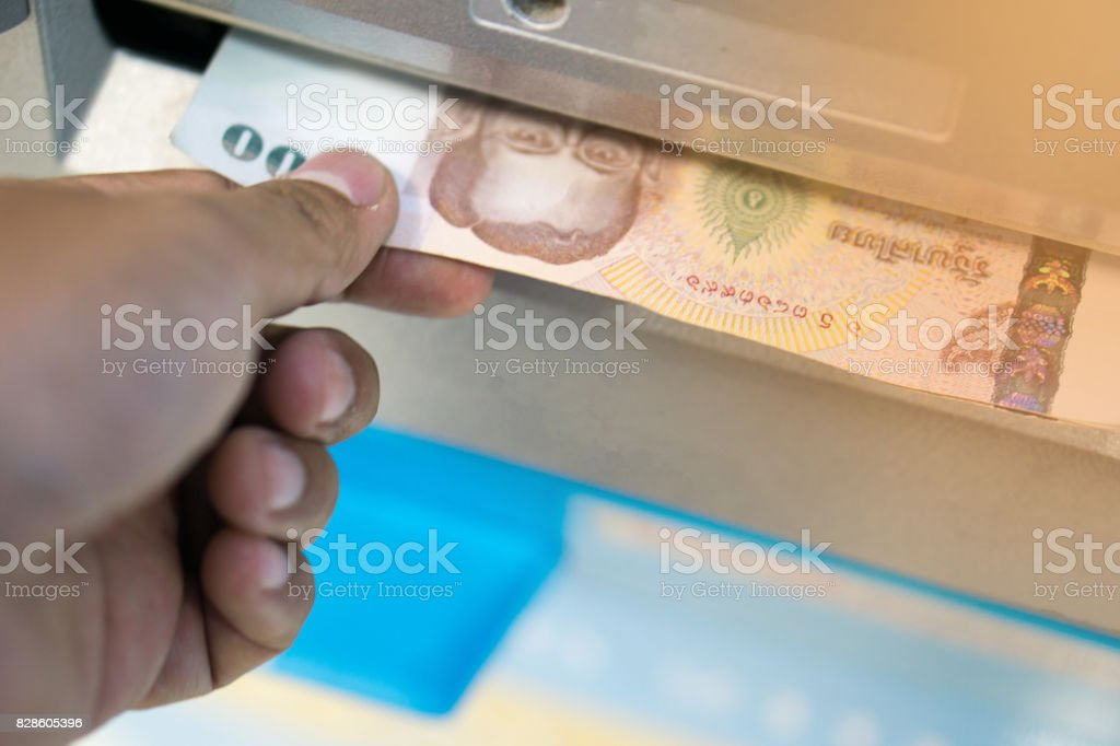 man receive money from the automated teller machine.people withdraw money from ATM and get it from money box or dispenser at cash point with light stock photo
