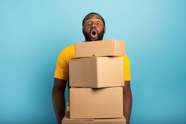 Man receives a lot of packages and has a surprised expression. Cyan background stock photo