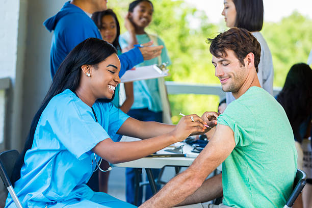 Man receives immunization at outdoor free clinic Mid adult Caucasian man smiles as African American nurse gives him a shot in his left arm. He is receiving a free medical exam and immunizations at a community outdoor free clinic. Patients and volunteers are standing in the background talking. flu shot stock pictures, royalty-free photos & images