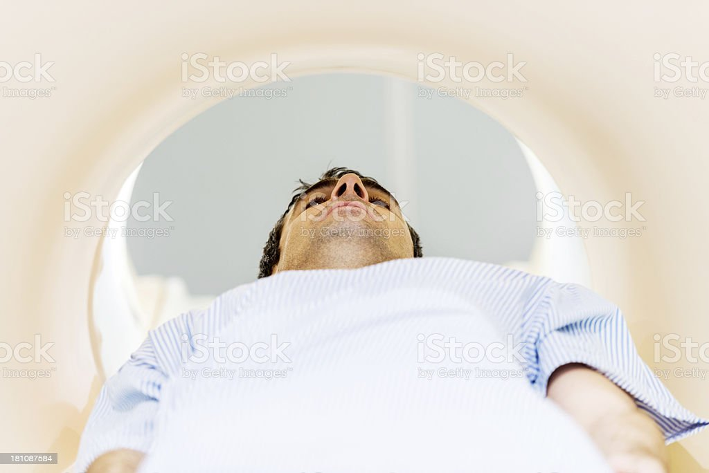 Man receiving an MRI Scan. Mid adult man lying down and receiving an MRI Scan.    30-39 Years Stock Photo