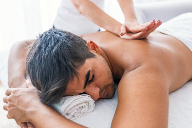 Man receiving back massage from masseur Portrait Of Man Receiving Massage Treatment From Female Hand. Close-up of masseur's hands and a client's back. Man getting relaxing massage in spa. Man receiving back massage from masseur massage stock pictures, royalty-free photos & images