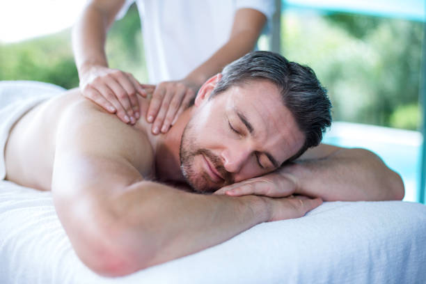 man receiving back massage from masseur - massaggio foto e immagini stock