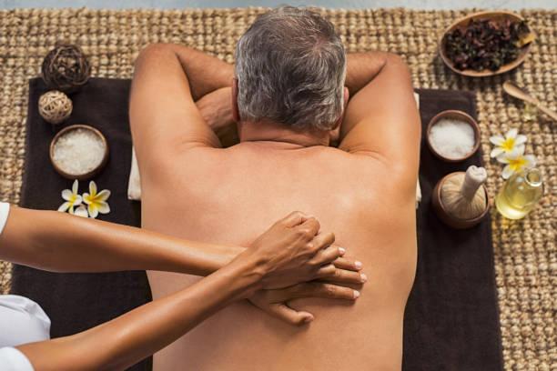 mann empfangen rückenmassage - chiropraktik wellness stock-fotos und bilder