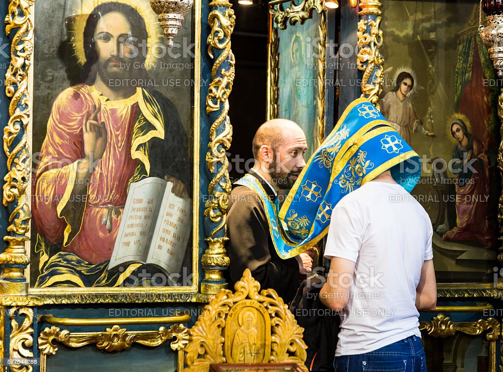 Man receiving confession in an orthodox church, Bucharest, Romania stock photo