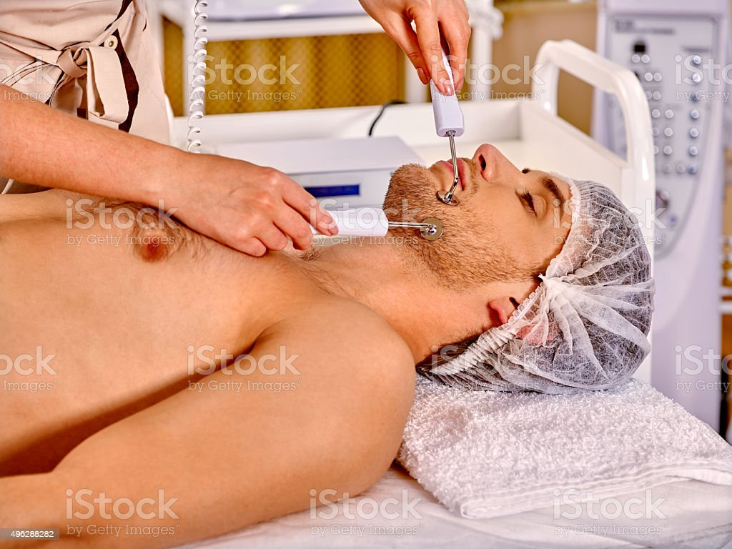 Man receiving electric facial peeling hydradermie massage stock photo