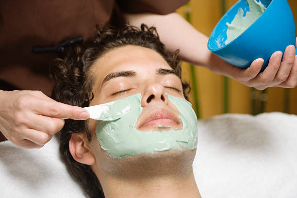 Man receiving green mud mask from beautician stock photo