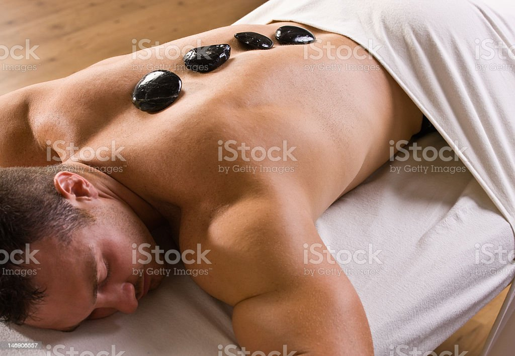 Man receiving hot stone therapy massage royalty-free stock photo