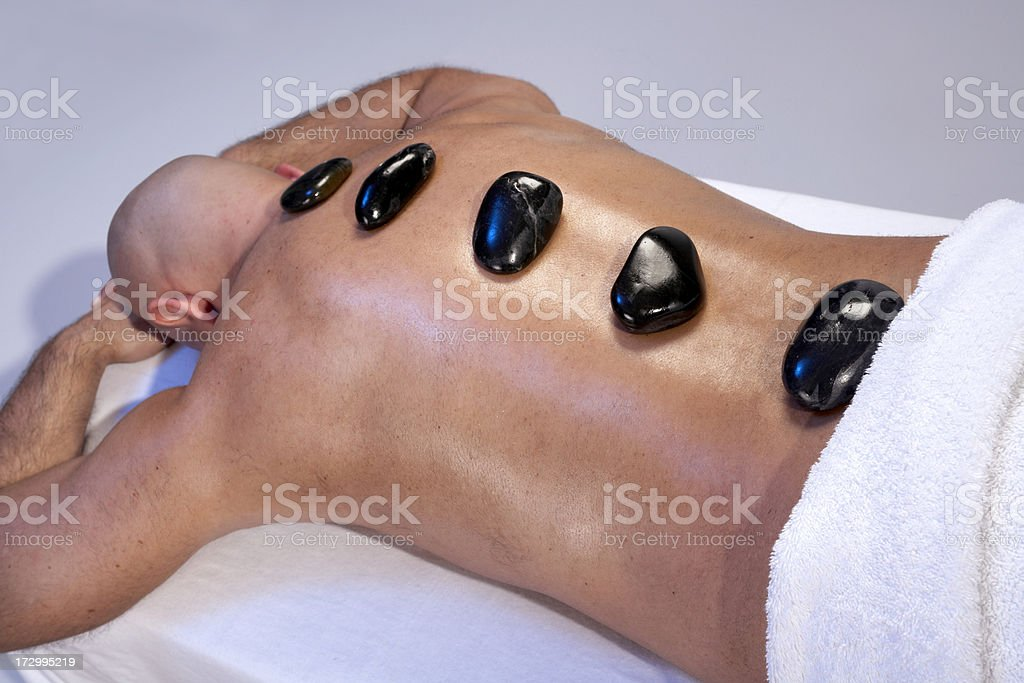 Man receiving hot stones massage royalty-free stock photo