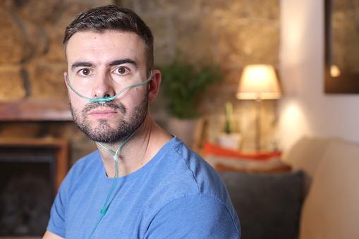 Man receiving oxygen through nasal tube.