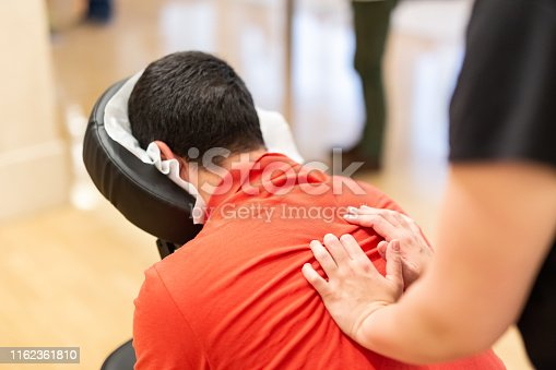 Man seated in a massage chair for back massage.