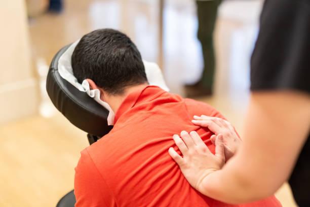 Hombre recibiendo shiatsu en una silla de masaje rápido - foto de stock