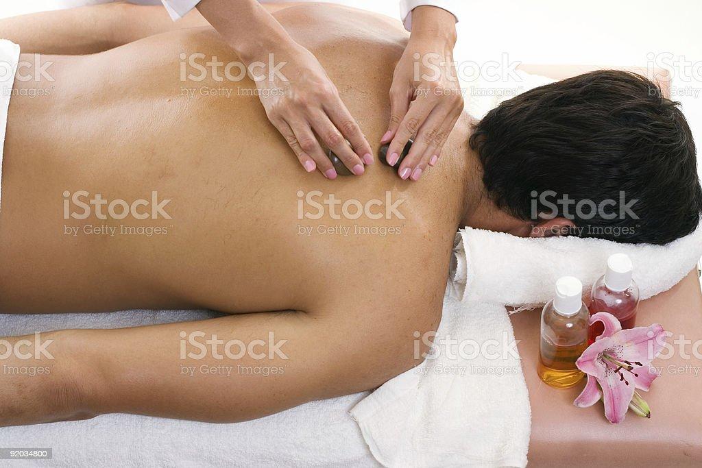 Man receiving thermal stone massage royalty-free stock photo